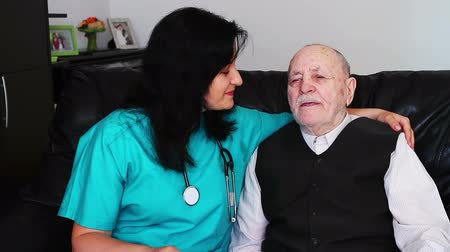 fizjoterapeuta : Nurse giving care to a senior man Wideo