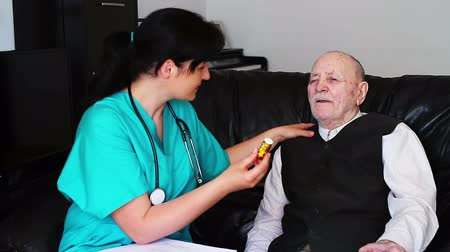 prescrição : Nurse giving pills to a senior man Vídeos