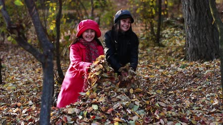 fall down : Two girls throwing fall leaves in autumn park