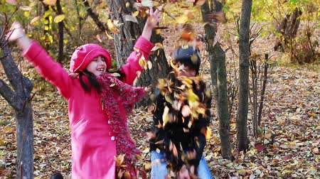 fall down : Girls playing in Autumn with leaves