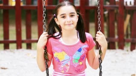 зубастая улыбка : Little girl on swing smiling at camera in summer playground Стоковые видеозаписи