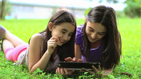 devices : Girls playing on digital tablet outdoors Stock Footage