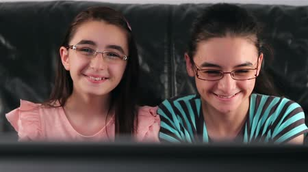 two seater : Happy teen girls with glasses watching tv