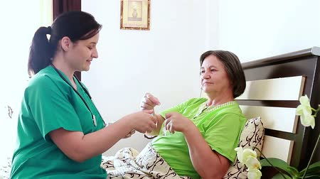 бабушка : Nurse giving to senior woman the pill capsules from the box. Focus on patient.