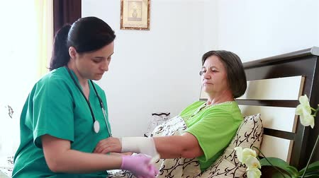 opieka : Nurse bandaging up an injured senior woman arm in retirement home. Focus on patient