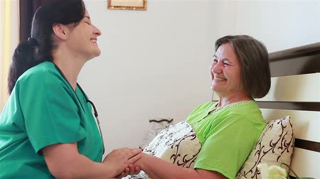 śmiech : Senior woman talking and laughing  with her home caregiver nurse. Focus on patient.