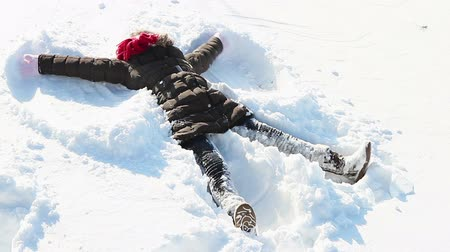 snow angel : Little girl making angels in the snow and having lots of fun. Stock Footage