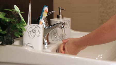 mosás : Little girl washes her hands in the bathroom.