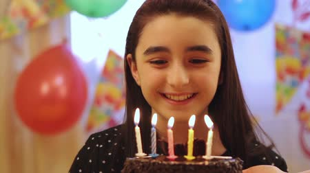 üfleme : Happy young girl blowing out candles on a birthday cake.