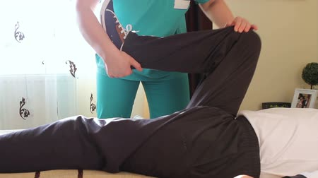 física : Physical therapist working rehabilitation exercises for legs with immobilized patient.
