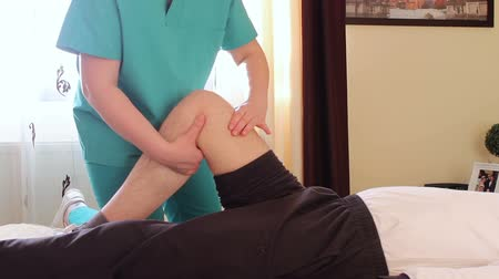 kolano : Physical therapist giving a knee massage to young man.