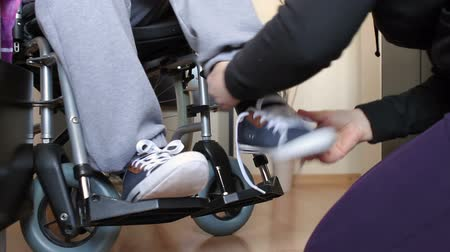 rokkant : Helping a disabled young man in wheelchair get dressed. Stock mozgókép