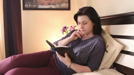 ler : Christian woman reading the Holy Bible in her bedroom Vídeos