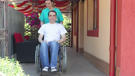 rokkant : Nurse walking with male patient in a wheelchair outdoors