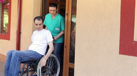 hemşirelik : Nurse with young man in wheelchair going for a walk