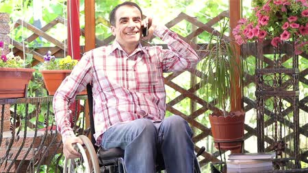 rokkant : Happy young man in a wheelchair talking on the smartphone outdoors