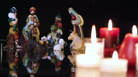 church of the nativity : Christmas nativity scene with candles on black background. The focus moves from candles to figurines. Stock Footage