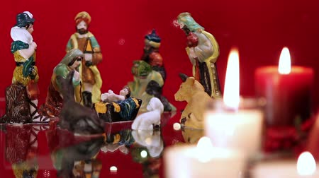 jézus : Christmas nativity scene with candles on red background with lights. The focus moves from candles to figurines. Stock mozgókép