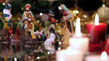 ježíš : Christmas nativity scene with candles in front of Christmas tree. The focus moves from candles to figurines. Dostupné videozáznamy