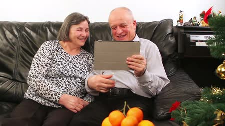 в чате : Seniors couple using tablet computer talking with video chat on Christmas.