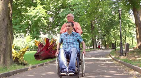 caregiver : Father walking with his disabled young son in the park.