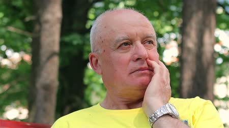 одиноко : Sad senior man thinking about something on a bench in the park.