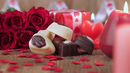 čokolády : Red roses and chocolate candies with candles on wood for Valentines Day. Love and romance concept.