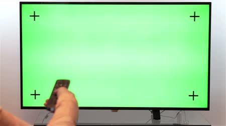 tv screen : Woman hand with TV remote switching channels on a green screen TV point of view with luma matte.