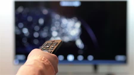çevirmek : Television remote control changes channels thumb on smart TV screen.