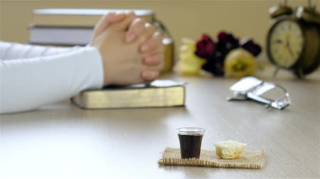 de sangue puro : Woman praying before taking communion. The blood and the bread elements are in front focus. Closeup shot. Stock Footage
