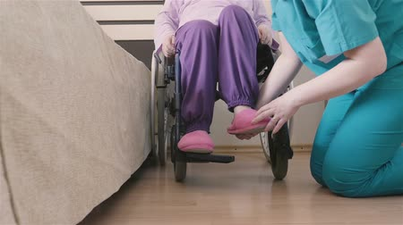 caregiver : Young nurse caring of elder disabled woman in wheelchair and going for a walk. Home or hospice nursing and assistance concept. 4K footage at 60fps.