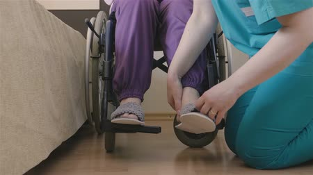 rokkant : Young female caregiver helping senior woman in wheelchair to put her shoes. Giving assistance and nursing concept. 4K footage at 60fps.