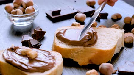 Spreading hazelnut chocolate cream on bread closeup. Delicious breakfast concept. Stock mozgókép