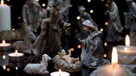 mary : Christmas manger nativity scene with figures and atmospheric candles lights. Dolly shot in 4k.