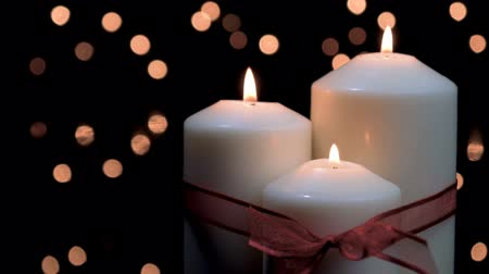 Christmas candles with red ribbon burning in atmospheric light. 4k