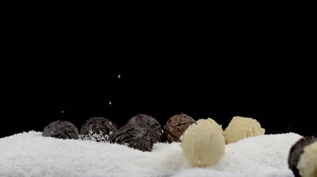 yermantarı : Chocolate truffles falling in coconut flakes on black background. Slow motion at 180 fps. Stok Video
