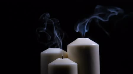 Three extinguished candles with smoke on a black background. Slow motion at 180fps. Stock mozgókép