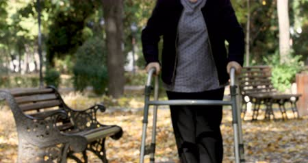 Senior woman with walker getting up from bench and walking outdoors in autumn park. The person comes in focus.