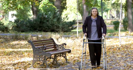 Senior woman walking with walker in autumn park. The person is out focus but comes in focus gradually. Stock mozgókép