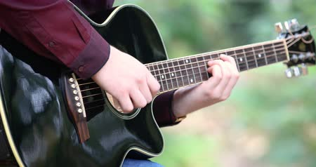 Young mans hands playing acoustic guitar artist musician outdoors