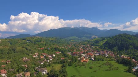 Aerial view from above over small village in mountains. Beautiful landscape in summer day. 4k