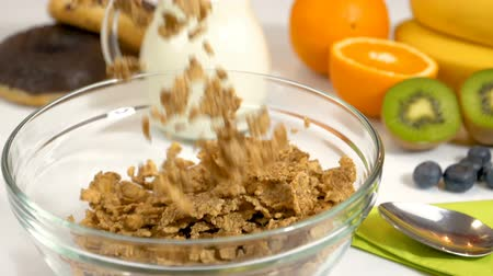 Cereals flakes falling in glass bowl for healthy and organic breakfast. Slow motion shot.