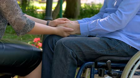 Closeup of disabled young man hands encouraged by his wife outdoors. Support and care concept. Slow motion 4k