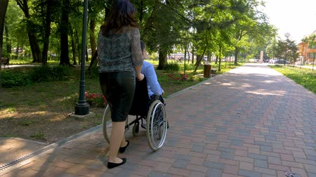 Young man on wheelchair walking with his wife outdoors in park. 4k