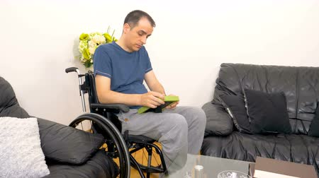 Melancholic sad young disabled man in wheelchair looking at a photo. 4k
