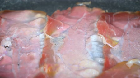 Closeup of bacon strips frying on a grill in slow motion.