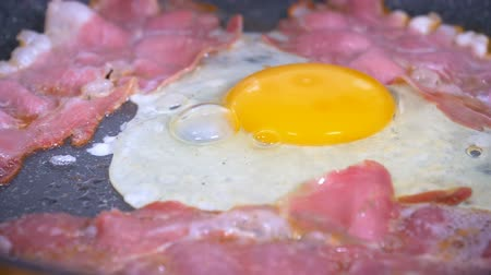 Egg and slices of bacon frying in the hot pan. Egg being dropped on fried bacon in slow motion. Stock mozgókép