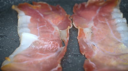 Close up of slices of bacon lays on the hot grill being fried. Slow motion footage.