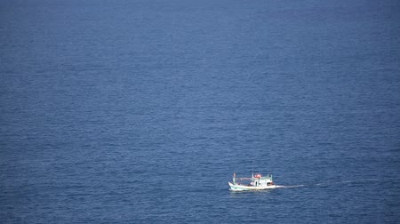 fisherman : The panoramic view of blue ocean with the fishing boat sailing from right to left screen