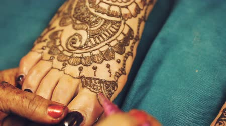 concentrando : Henna artist (Mehndi) painting the tattoo pattern on the foot of indian bride on the indian wedding day